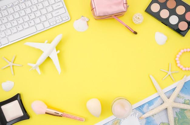 Lay plat de fond jaune avec des accessoires de voyage