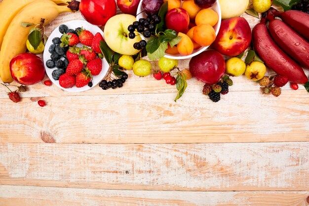 Lay plat de fruits sur un fond en bois blanc.