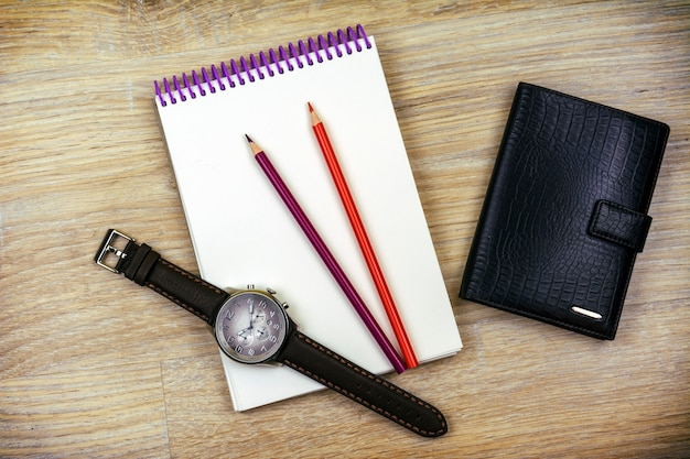Lay plat. la montre-bracelet pour hommes, le bloc-notes, deux crayons et un portefeuille pour hommes reposent sur la texture du bois