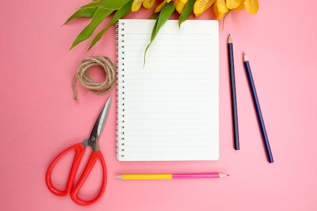 Lay plat de papier de cahier ouvert sur rose.