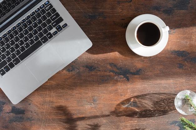 Lay plat de portable sur un bureau en bois vintage, vue de dessus sur le bureau avec des ombres