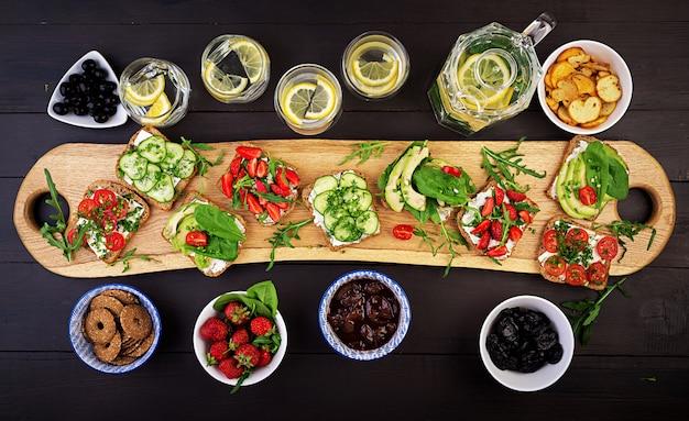 Lay plat de réglage de la table de dîner végétarien sain. sandwichs à la tomate, concombre, avocat, fraise, fines herbes et olives, snacks. propre manger, nourriture végétalienne