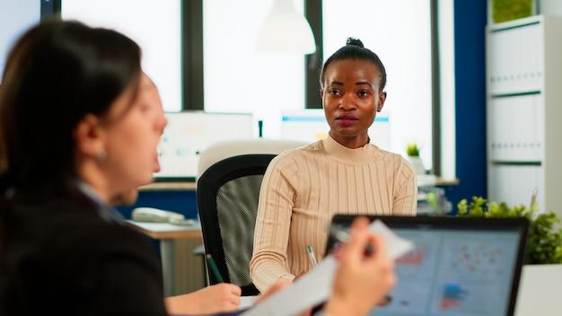 Un leader africain confiant négocie avec un groupe d'entreprises expliquant les avantages du contrat lors d'une réunion formelle du conseil d'administration consultant les entreprises clientes présentant une offre commerciale assis au bureau de la conférence tabl