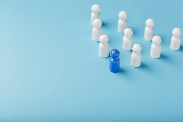 Le leader en bleu mène un groupe d'employés blancs vers la victoire, les rh, le recrutement du personnel. le concept de leadership.