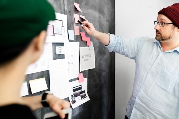 Leader dans une entreprise en démarrage remue-méninges à l'aide d'un tableau noir