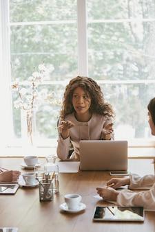 Leader. jeune femme d'affaires dans un bureau moderne avec équipe. réunion créative, attribution de tâches. les femmes travaillant au front-office. concept de finance, d'affaires, de pouvoir des filles, d'inclusion, de diversité, de féminisme.