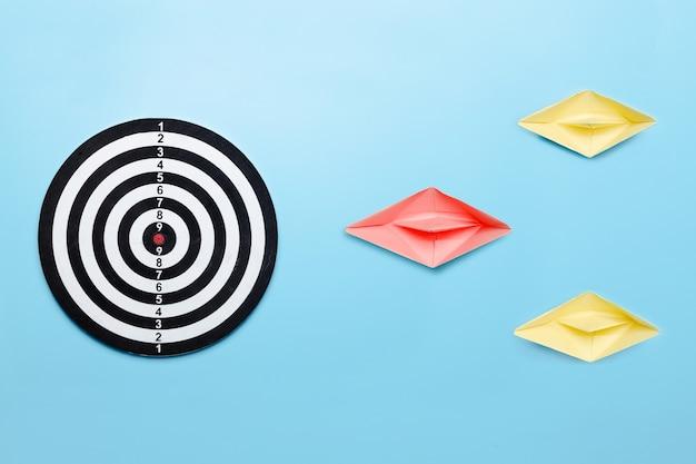 Un leader professionnel mène à la cible du concept d'entreprise, guide du patron du papier du bateau avant le jeu de fléchettes