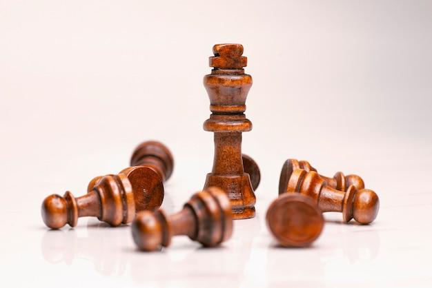 Le leadership des échecs est le roi du bois. des idées de travail d'équipe pour réussir les idées d'échecs aident le roi et sauvent la stratégie