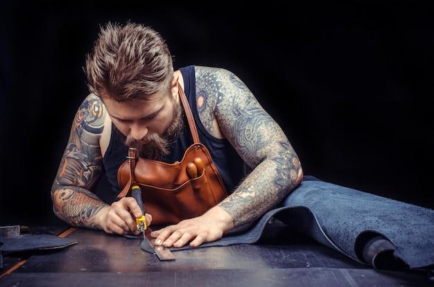 Leather currier crée un nouveau produit en cuir dans son atelier de cuir./leather craftsman produit un bon produit.