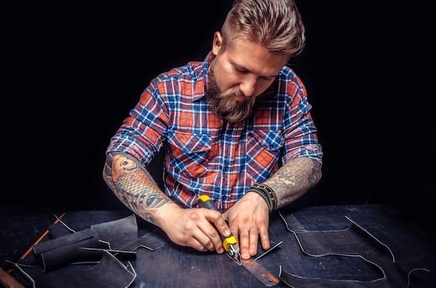 Leather currier crée un nouveau produit en cuir sur le lieu de travail.
