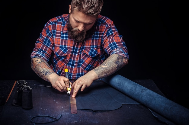Leather tanner travaillant avec du cuir à l'aide d'outils d'artisanat sur le lieu de travail