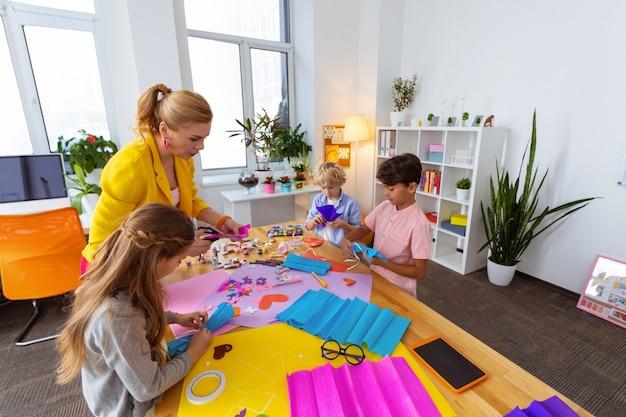 La leçon d'art. des écoliers mignons et intelligents se sentent joyeux tout en faisant des découpes à la leçon d'art