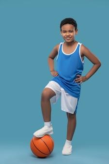 Leçon avec ballon. joyeux garçon à la peau foncée en chemise de sport et short tenant le ballon avec son pied debout de bonne humeur