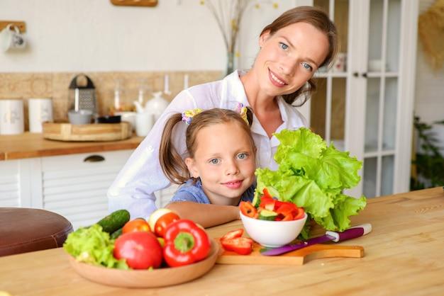 Leçon de cuisine une maman patiente heureuse apprend à sa petite fille à cuisiner des aliments sains