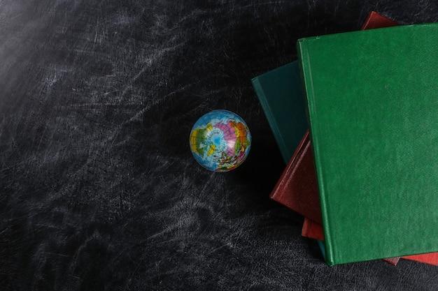 Leçon de géographie. une pile de livres et un globe sur un tableau noir. vue de dessus