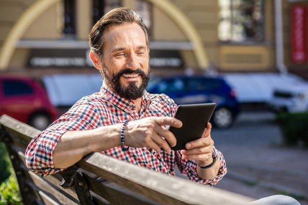 Lecteur avide. enthousiaste barbu assis sur le banc en lisant un livre électronique