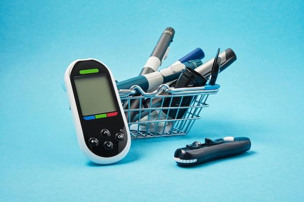 Lecteur de glycémie et plusieurs stylos seringues différents pour les injections d'insuline sur fond bleu