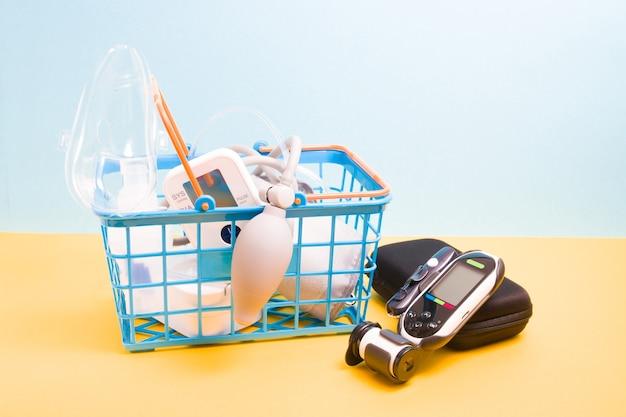 Lecteur de glycémie se trouve à côté d'un petit panier bleu dans lequel se trouvent un nébuliseur pour inhalation et mesurer le tensiomètre