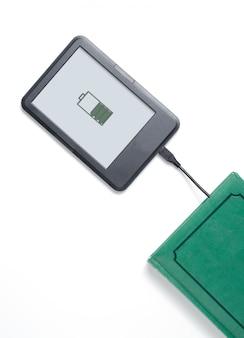 Lecteur de livre électronique et livre vert reliés par un câble.