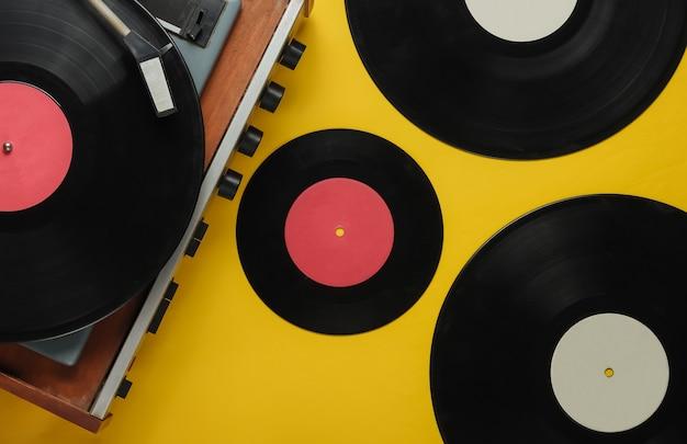 Lecteur de vinyle à l'ancienne avec des disques sur fond jaune
