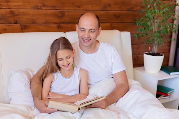 Lecture en famille. papa lit un livre à sa fille avant d'aller se coucher