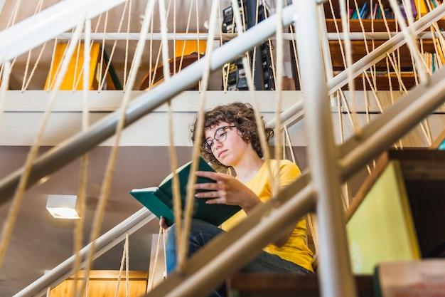 Lecture femme assise dans les escaliers avec un livre