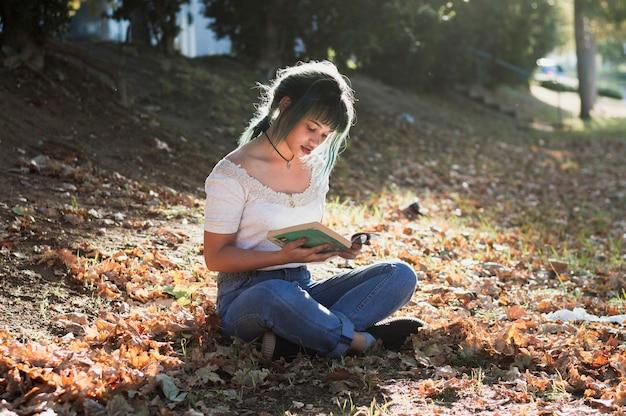 Lecture de fille sur une colline ensoleillée