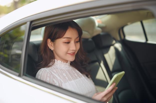 Lecture d'informations depuis un smartphone. une femme d'affaires intelligente est assise à l'arrière de la voiture de luxe avec un intérieur noir.