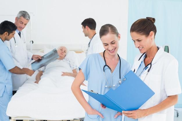 Lecture de rapport avec des collègues et un patient derrière