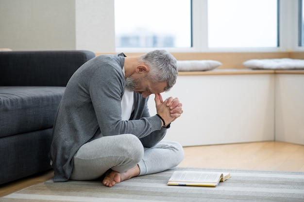 Lectures spirituelles. un homme aux cheveux gris assis sur le sol et à la réflexion