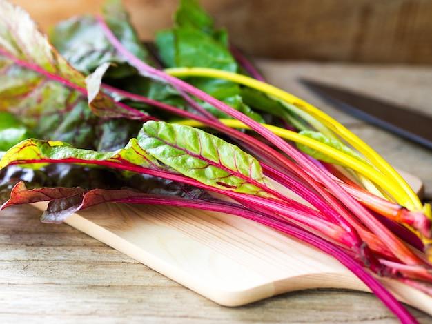 Légume arc-en-ciel frais de bette à carde sur planche de bois se préparant à la cuisson.