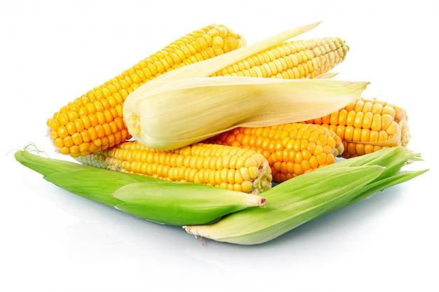 Légume de maïs frais avec des feuilles vertes isolées