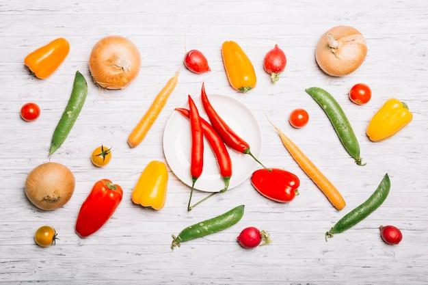 Légumes allongés autour de la plaque avec du piment