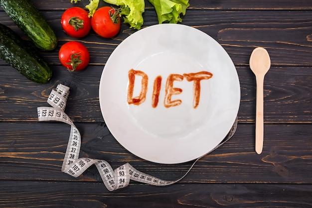 Légumes assortis avec un ruban à mesurer et une assiette avec le mot
