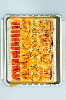 Légumes au four, carottes, pommes de terre, poivron jaune et courgettes, tranchés, avec de l'huile d'olive, sel, poivre, sur une plaque à pâtisserie. coup de tête.