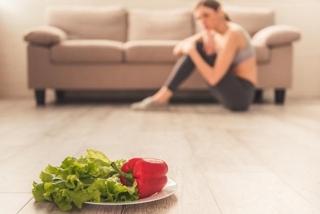 Légumes au premier plan, fille déprimée est assise.