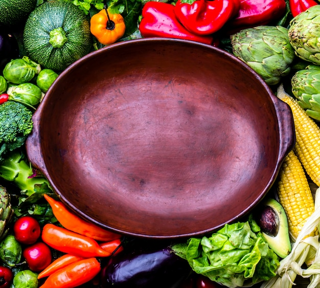 Légumes biologiques frais autour d'un pot en argile vide