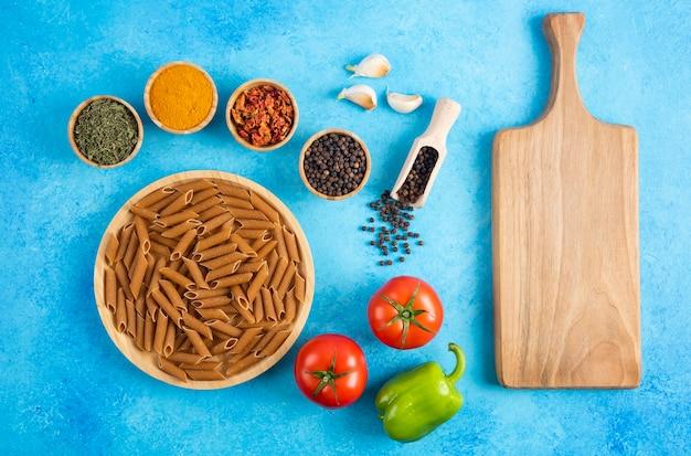 Légumes biologiques frais avec pâtes crues et épices. planche de bois sur fond bleu.