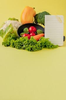 Légumes et cahier avec fond blanc. bio alimentation saine, légumes biologiques sur jaune