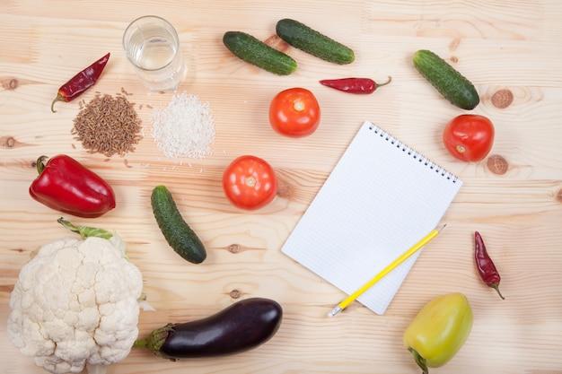 Légumes et céréales et cahier sur une table en bois