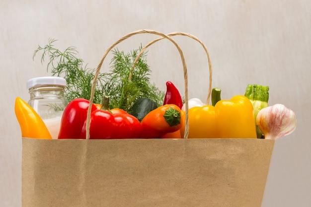 Légumes colorés et bouteille de lait dans un sac en papier. fermer. fond beige