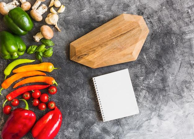 Légumes colorés sur une planche en bois avec cahier à spirale et planche de bois sur fond de béton