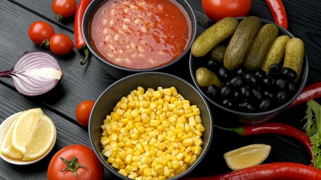 Légumes en conserve dans une assiette. concombre, maïs, haricots. sur un tableau noir