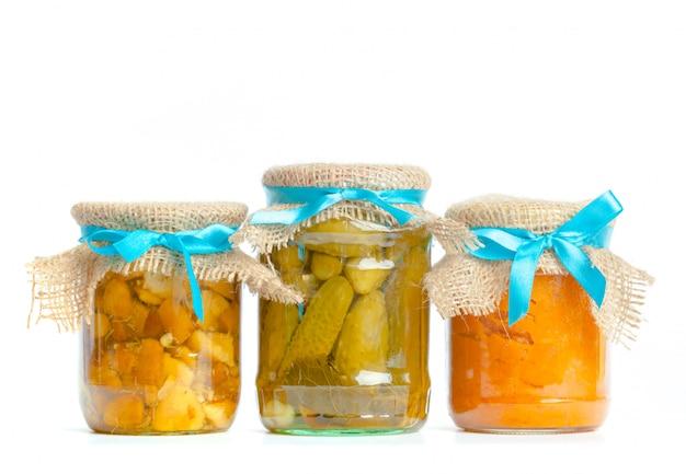 Légumes en conserve dans des bocaux en verre isolé sur fond blanc