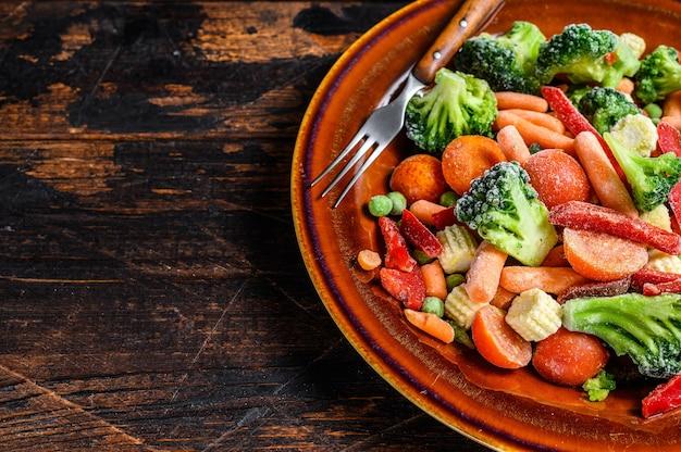 Légumes coupés surgelés, brocoli, poivrons doux, tomates, carottes, pois et maïs sur une assiette