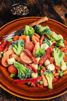 Légumes coupés surgelés, brocoli, poivrons, tomates, carottes, pois et maïs sur une assiette. sombre
