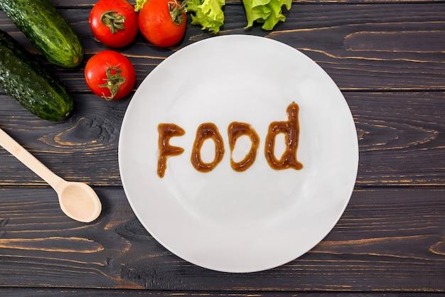 Des légumes, une cuillère en bois et une assiette blanche avec le mot food. vue d'en-haut.