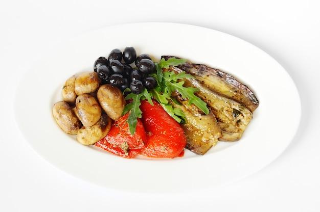 Légumes cuits au feu sur une plaque blanche ene fond blanc