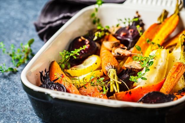 Légumes cuits au thym dans le plat à four, fond bleu.