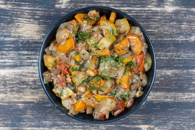 Légumes cuits dans un bol noir sur table en bois, gros plan, vue de dessus